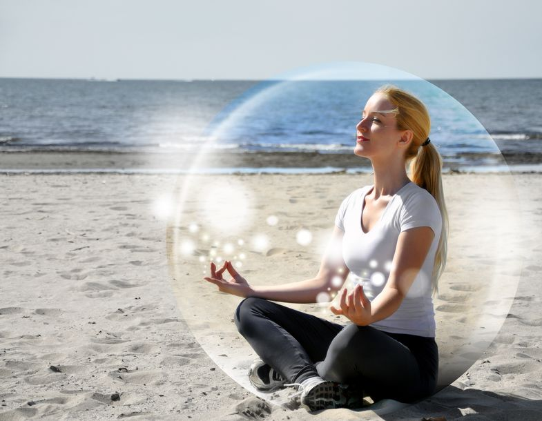 17352449 - a woman is sitting on the beach inside a bubble with peace and tranquility  she is meditating and there are sparkles